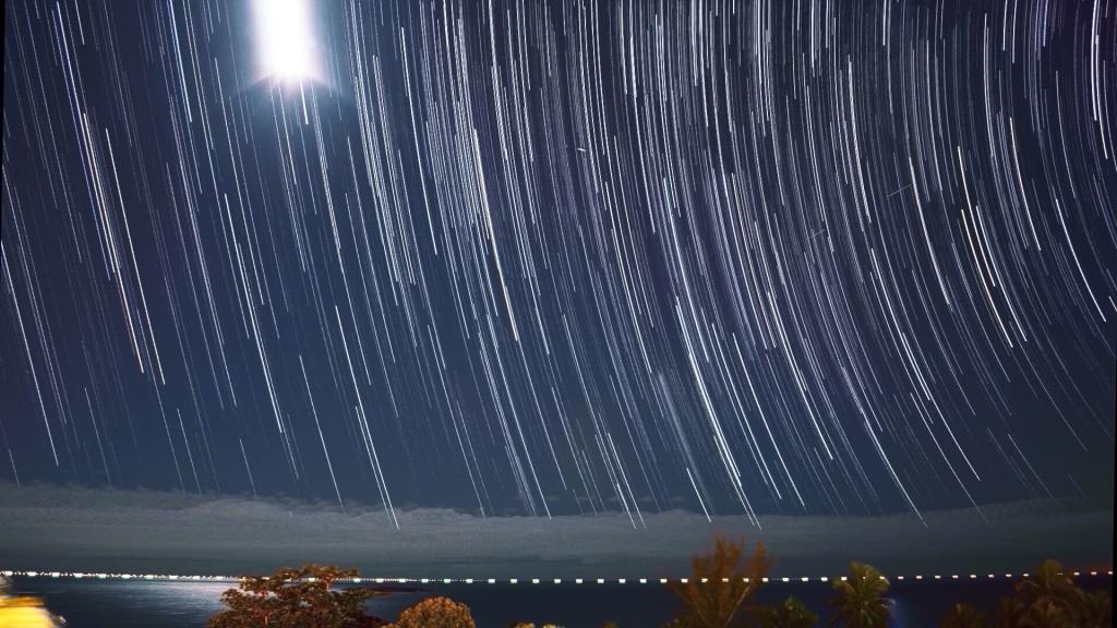 """""""Stars-Trail"""", Lua (superior-esquerda), satélite (tracejado, diagonal direita), """"flare"""" (Iridium?, centro-superior), navios (horizonte)"""